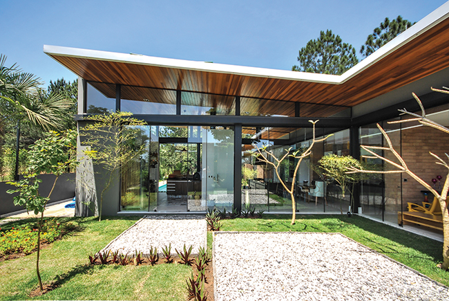 Portas de correr encarregam-se de integrar a casa com os jardins e a piscina