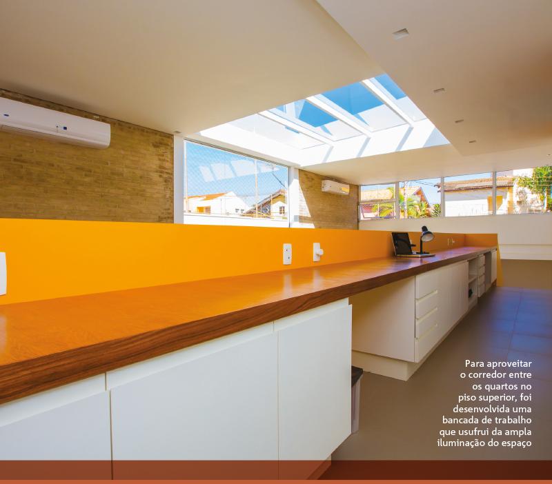 Para aproveitar o corredor entre os quartos no piso superior, foi desenvolvida uma bancada de trabalho que usufrui da ampla iluminação do espaço