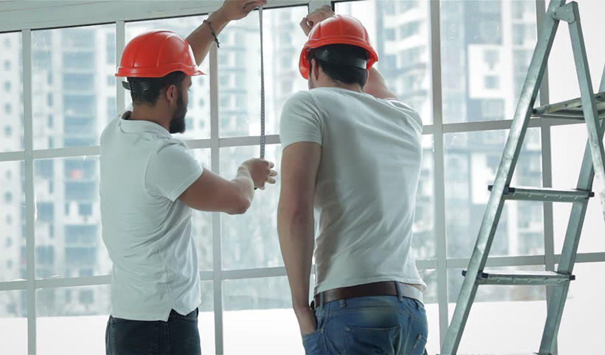 dois vidraceiros instalando uma janela