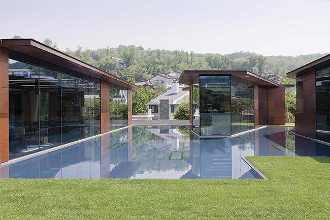 O espelho d'água exerce função simultânea de conectar e dividir os pavilhões envidraçados